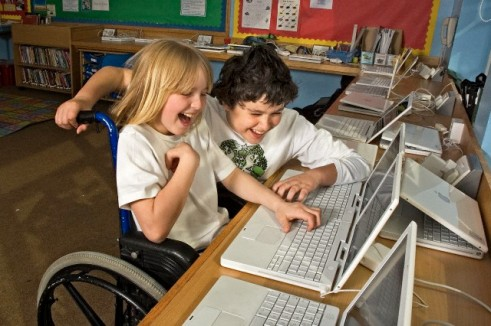 Disabled boy in wheelchair with friend using laptop computer